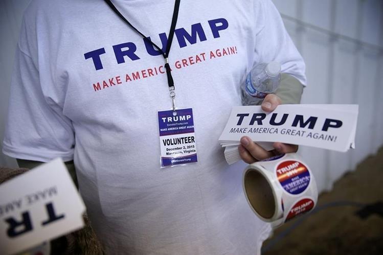 Una simpatizante de Donald Trump sostiene promocionales de la campaña rumbo a la presidencia de EE. UU. (Foto Prensa Libre: AFP).