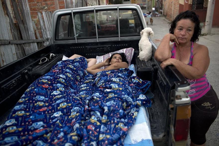 Dos mujeres heridas esperan ser llevadas a un hospital, junto a ellas su mascota, amiga inseparable. (Foto Prensa Libre: AP).