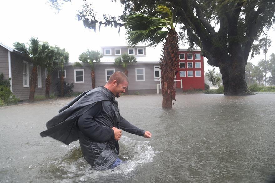 Un hombre huye de la inundación causada por el huracán Matthew en una zona residencial de Florida, EE. UU. (Foto Prensa Libre: AFP).