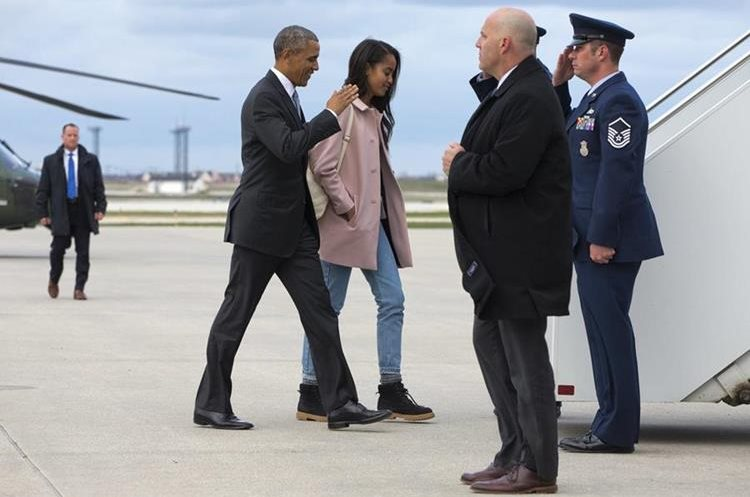 President Barack Obama salutes as he and daughter Malia Obama board Air Force One, Thursday, April 7, 2016, leaving Chicago en route to Los Angeles. (AP Photo/Jacquelyn Martin)