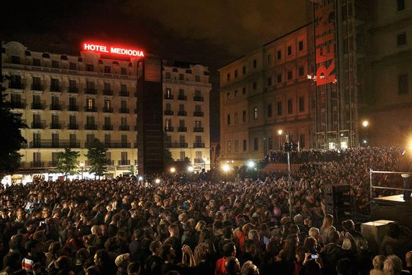 Personas escuchan un discurso de Pablo Iglesias, líder de Podemos quienes celebran los resultados obtenidas en las elecciones municipales de ayer. (Foto Prensa Libre: AP).