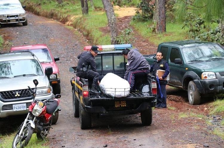 Agentes policiales trasladan el cuerpo sin vida del hombre en un autopatrulla. (Foto Prensa Libre: Héctor Cordero)