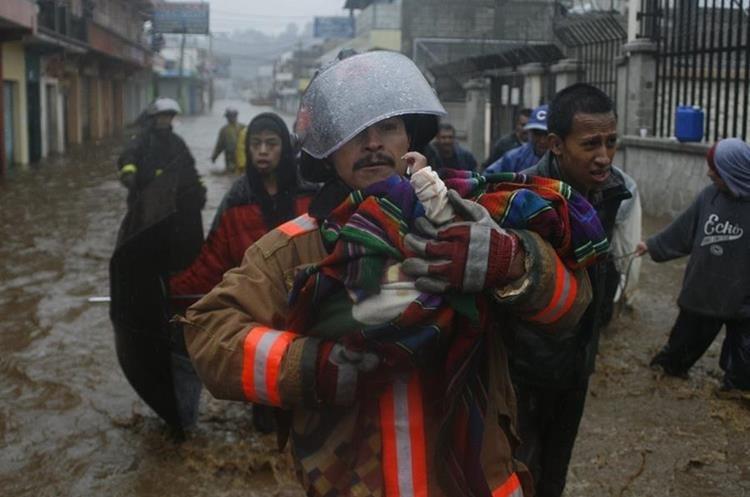Un bombero voluntario pone a salvo a un bebé de cinco meses, que junto a su familia quedó atrapado en su vivienda, en la 6a. calle de la zona 2 de Quetzaltenango. La inundación en ese sector afectó a 200 hogares. (Foto: Hemeroteca PL)