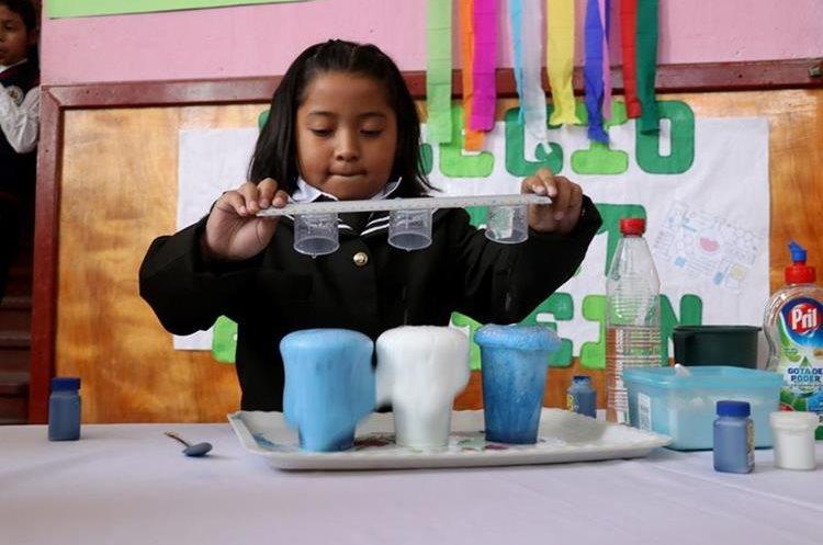 Fernanda Rivas Cardona de primero primaria muestra su proyecto denominado la bandera espumosa. (Foto Prensa Libre: Mike Castillo).