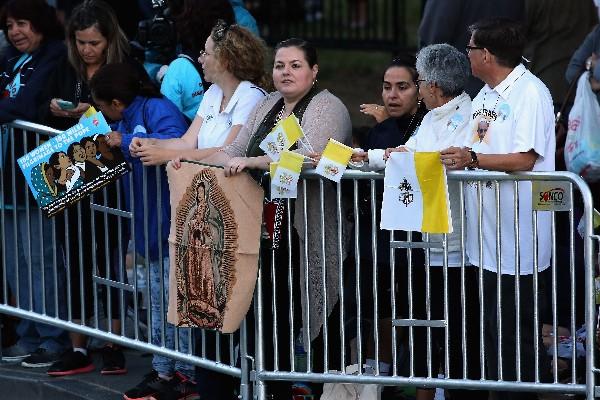Una mujer sostiene una imagen de la virgen María como ella y otros se reúnen para ver al Papa.