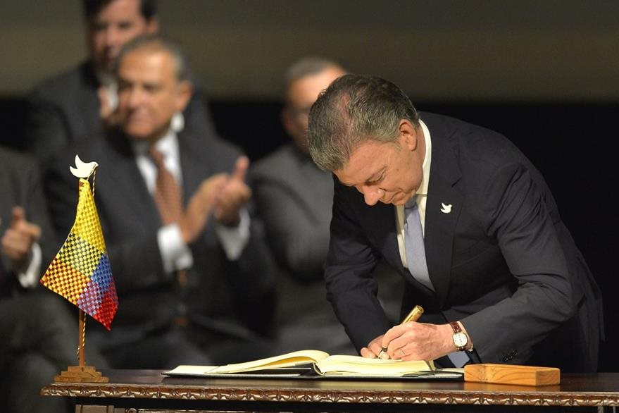 El presidente de Colombia, Juan Manuel Santos, rubrica el nuevo acuerdo. (Foto Prensa Libre: AFP).