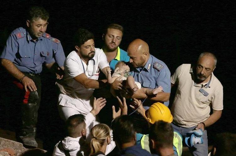 Miembros de rescate encuentran a un bebé de siete meses tras el terremoto en la isla Ischia en Italia. (Foto Prensa Libre: EFE)