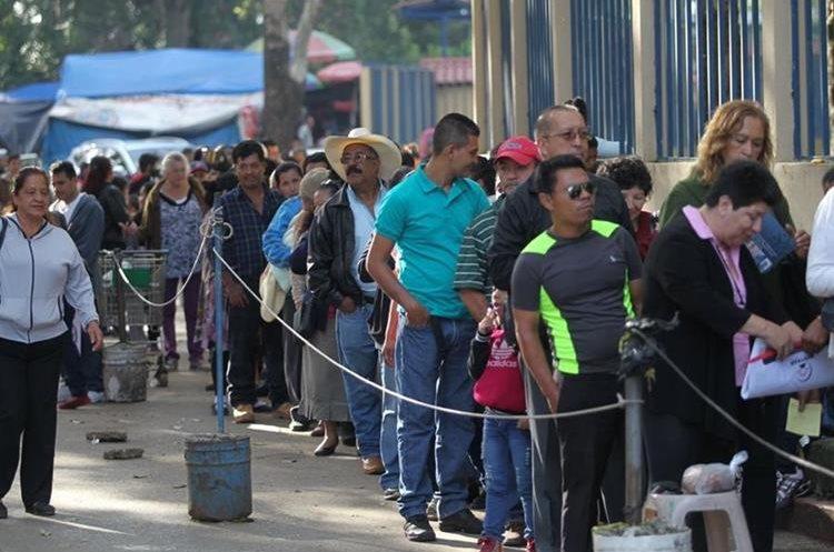Una larga fila de personas espera ingresar debido a los controles que se llevan a cabo.