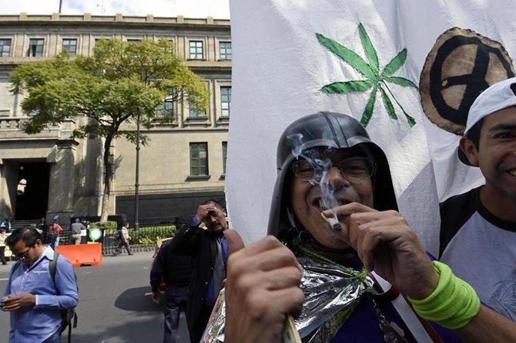 Un hombre fuma marihuana en las afueras de la Suprema Corte de Justicia de México despué de conocer su decisión. (Foto Prensa Libre: AFP).