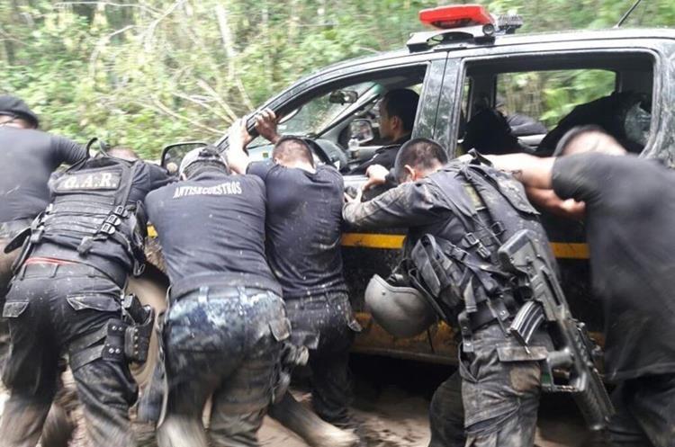 Agentes de la PNC empujan autopatrulla atascado en camino en la selva de la Biosfera Maya, Petén. (Foto Prensa Libre: PNC)