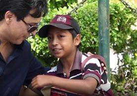 Agradecido con el regalo, un pequeño vendedor de dulces y chicles abraza a Gerson Hernández.
