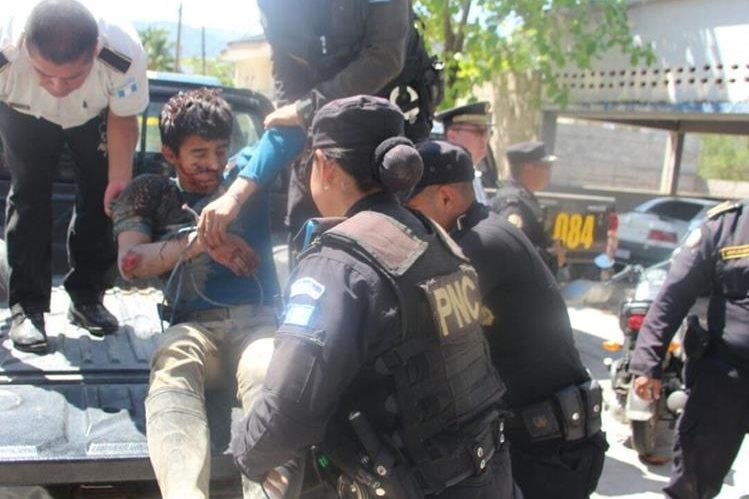 Uno de los sospechosos de haber violado y asesinado a una menor de 12 años en Camotán, mientras lo suben a un autopatrulla. (Foto Prensa Libre: Mario Morales)