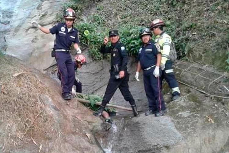 Socorristas resguardan el cuerpo del joven que murió al caer accidentalmente en un riachuelo. (Foto Prensa Libre: Whitmer Barrera)