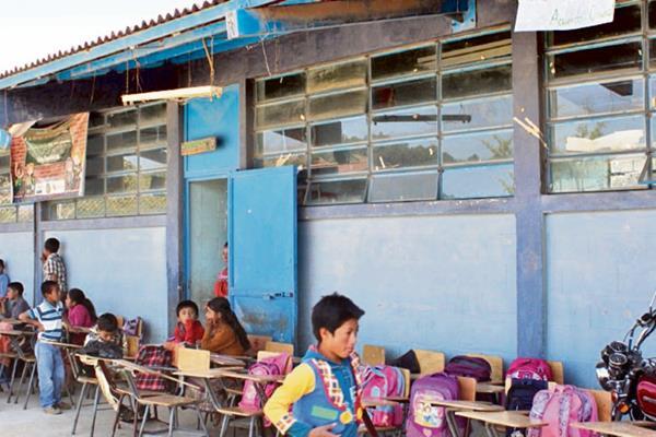 Niños reciben  clases en corredor de escuela,     porque el calor los afecta en una galera.
