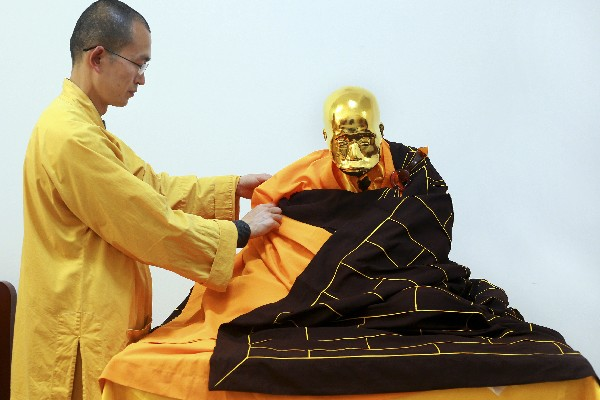 Zhen Yu pone un manto sobre el cuerpo momificado de Fu Hou. (AP).