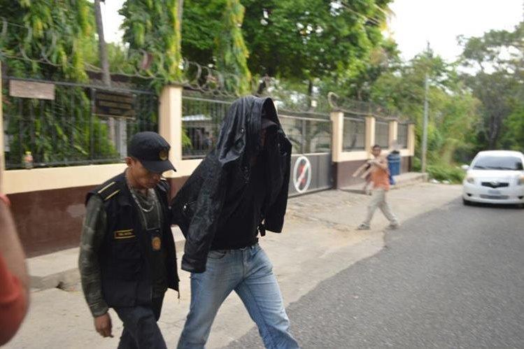 Uno de los agentes detenidos al salir del juzgado. (Foto Prensa Libre: Mario Morales)