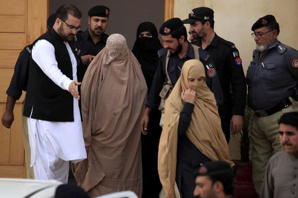 Agentes de seguridad paquistaníes escoltan a Sharbat Gula (c),en Peshawar. (Foto Prensa Libre:EFE).