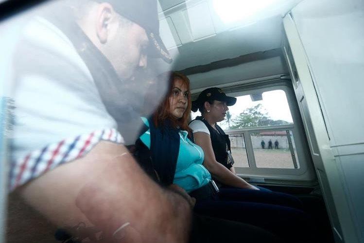 Agentes de la Policía Nacional Civil y Marixa Lemus, alias la Patrona, abordan un helicóptero en Jutiapa, después de que la sospechosa fue detenida en El Salvador y entregada a las autoridades guatemaltecas.