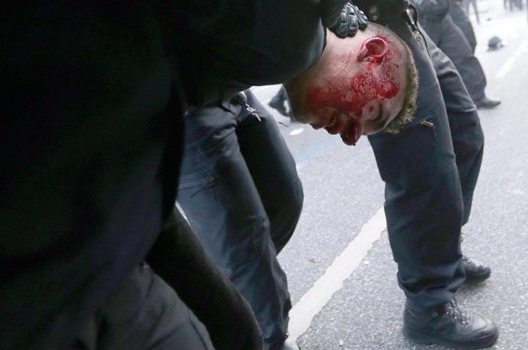 Un manifestante es sometido por la Policía. (Foto Prensa Libre: EFE)