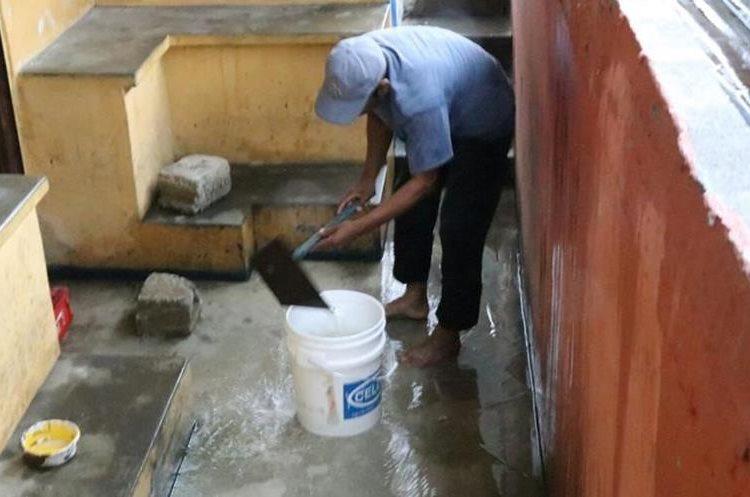 Un trabajador del estadio saca agua con una cubeta en la entrada a uno de los camerinos.
