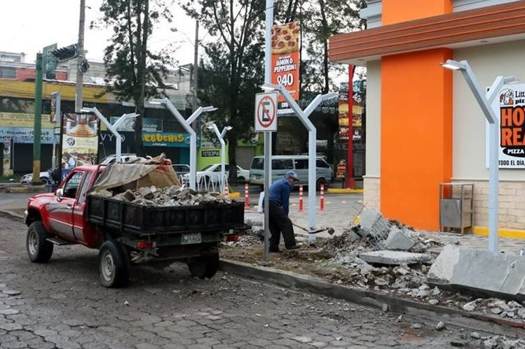 Un trabajadore retira restos de mesas y bancas frente a una pizzería que se halla en la zona 3 de Quetzaltenango. (Foto Prensa Libre: Carlos Ventura)