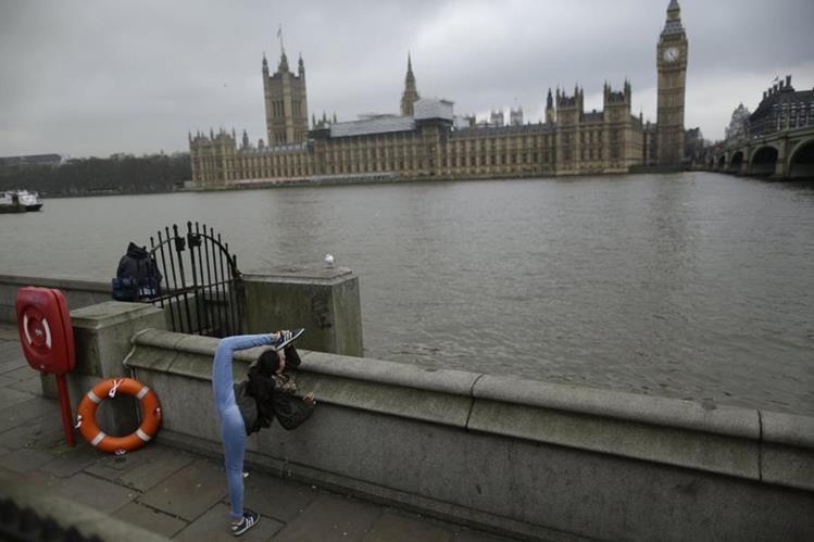 Una joven realiza ejercicios en la orilla del río Támesis frente al Parlamento en Londres.(AP)