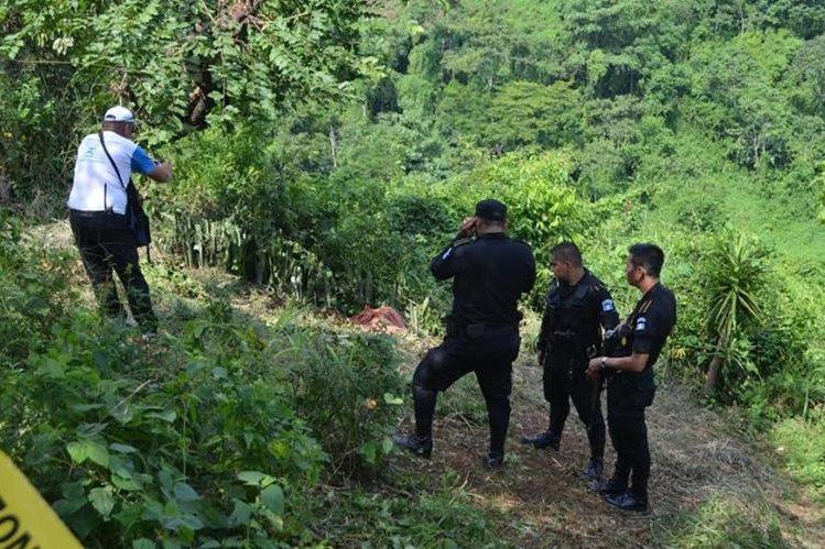 Autoridades inspeccionan el lugar donde quedó el cadáver de una de las víctimas, en El Asintal, Retalhuleu. (Foto Prensa Libre: Jorge Tizol)