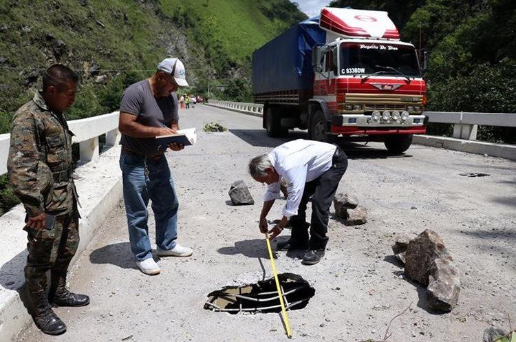 Personal del Ministerio de Comunicaciones mide uno de los nueve agujeros en el puente Selegua 2. (Foto Prensa Libre: Mike Castillo)