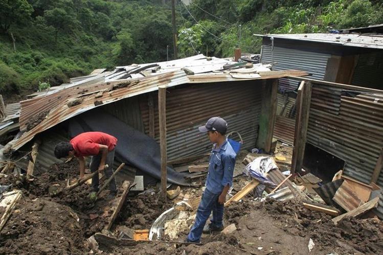 Marlon Iván López, de 19 años, remueve los escombros de lo que fue su casa en busca de documentos personales. (Foto Prensa Libre: Carlos Hernández)