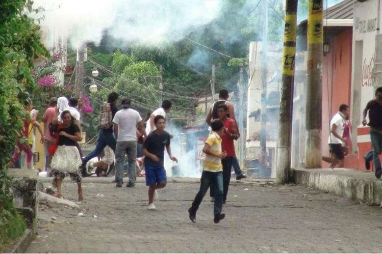 Manifestantes corren por gases lacrimógenos que agentes de la PNC lanzaron en manifestación en Cuyotenango, Suchitepéquez. (Foto HemerotecaPL)