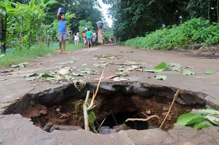 Dos agujeros que se formaron en la calle principal del cantón Recuerdo Ocosito, Retalhuleu, podrían dejar incomunicadas a unas 150 familias del sector. (Foto Prensa Libre: R. Miranda)