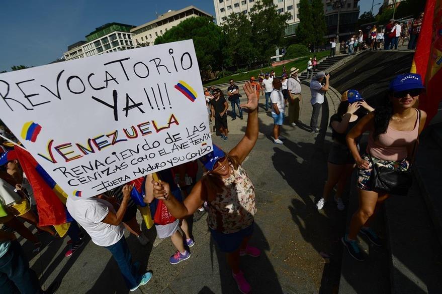 Manifestantes en Madrid, España, muestran pancartas contra el presidente de Venezuela, Nicolás Maduro. (Foto Prensa Libre: AFP).