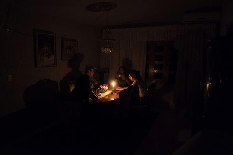 Una familia venezolana en Barinas cena a la luz de las velas debido a los constantes cortes de energía eléctrica que sufre el país. (Foto Prensa Libre: AFP).
