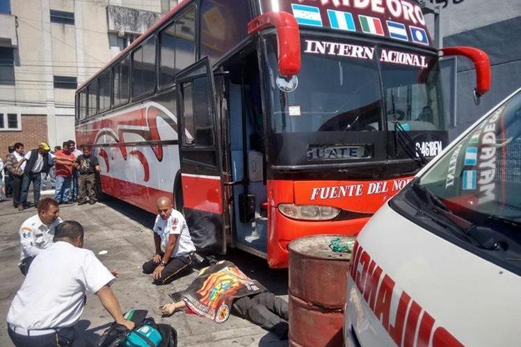 El cuerpo de un mecánico quedó tendido a una terminal de buses. (Foto Prensa Libre: Bomberos Voluntarios)