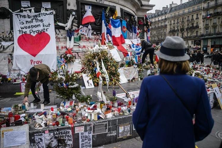 Velas y fotografías son llevadas por los franceses para recordar a las víctimas de la masacre. (Foto Prensa Libre: EFE).