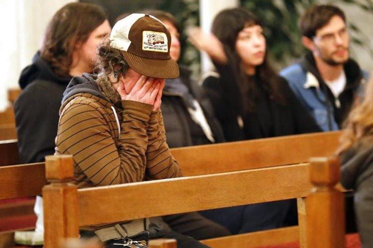 Una mujer, cuyos familiares aún están desaparecidos, llora en una iglesia en Oakland. (Foto Prensa Libre: EFE).