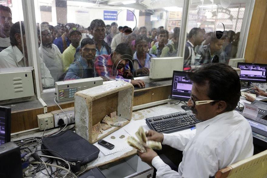 Un hombre atiende a varios clientes en una casa de cambio que es de las pocas en donde aún se aceptan billetes de alta denominación. (Foto Prensa Libre: AP).