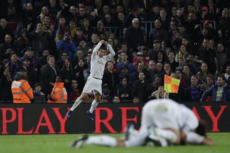 El portugués Cristiano Ronaldo celebra luego de marcar el gol del triunfo contra el Barcelona mientras algunos seguidores catalanes lo insultan. (Foto Prensa Libre: AFP)