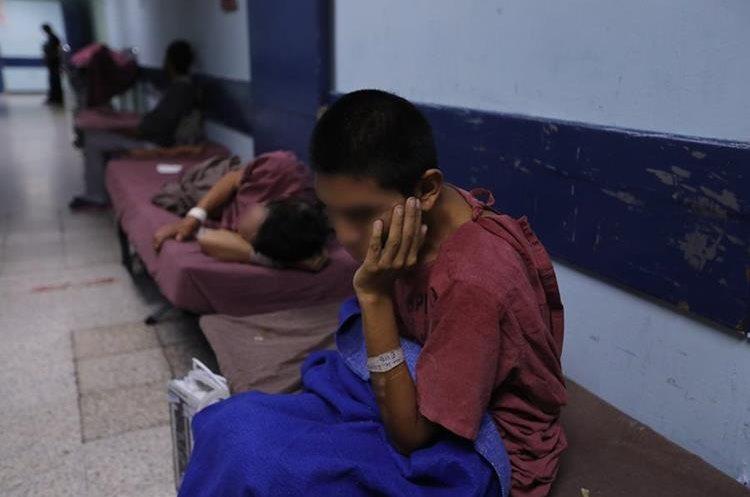 En un pasillo del hospital, en camillas armadas, esperan las personas que ya llevan varios días esperando cama por su delicada situación de salud.