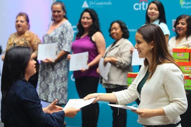 Isabel Martínez, gerente de mercadeo del Centro Comercial Portales, -de blanco- entrega diploma a una de las beneficiadas. (Foto Prensa Libre: Álvaro Interiano).