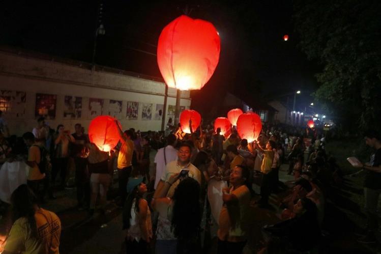 Familias de Retalhuleu participan en la elevación de globos luminosos de paperl para pedir deseos para el próximo año. (Foto Prensa Libre: Rolando Miranda)