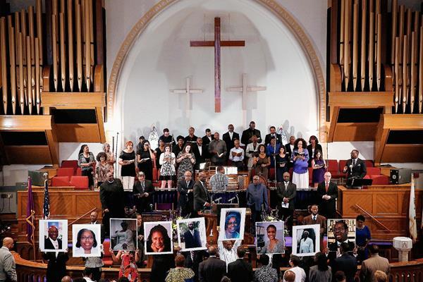 Fotografías de las nueve víctimas asesinadas en la iglesia Episcopal Metodista Emanuel, que familiares y amigos portaron durante una vigilia el jueves último. (Foto Prensa Libre: AFP).