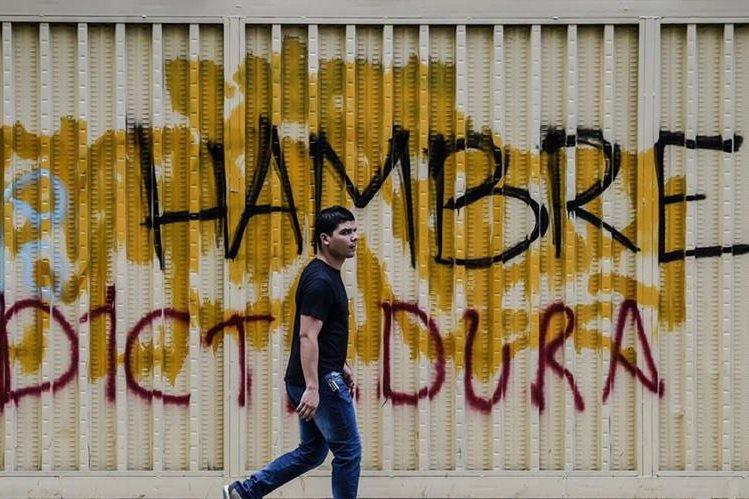Un venezolano pasa frente a un graffiti en Caracas, durante una huelga general. (AFP).