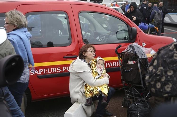 Una viajera abraza a su bebé afuera del Aeropuerto Orly, en París, evacuado luego que un hombre, que fue abatido, intentó desarmar a un soldado. (Foto Prensa Libre: AP)