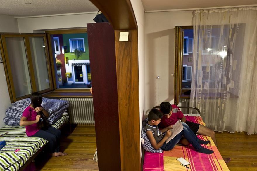 Dunia Qasu, 14, (izq.) se sienta en su cama, mientras que su hermano mayor Dilshad, 18, ayuda a su hermano menor Dildar, 11, en su tarea, en su apartamento en Elzach, Alemania. (Foto Prensa Libre: AP).