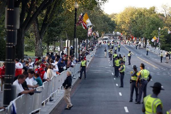 Varias personas frente al cordón de  seguridad para ver al Papa.