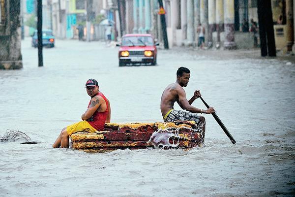 Dos hombres en una balsa improvisada cruzan una calle inundada  en La Habana,Cuba. (Foto Prensa Libre:AFP)