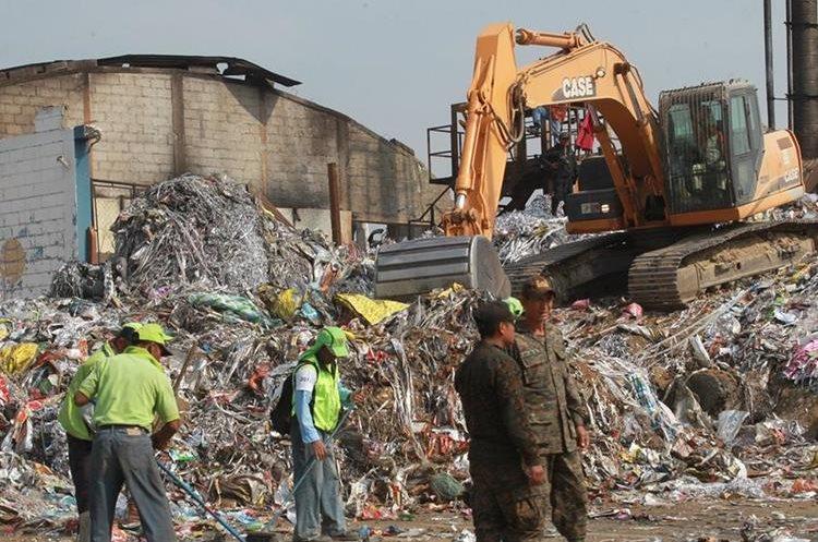 Trabajadores municipales y del Cuerpo de Ingenieros del Ejército retiran parte del material almacenado en la recicladora Ecoplast, S. A., en la zona 7 capitalina. (Foto Prensa Libre: Estuardo Paredes)