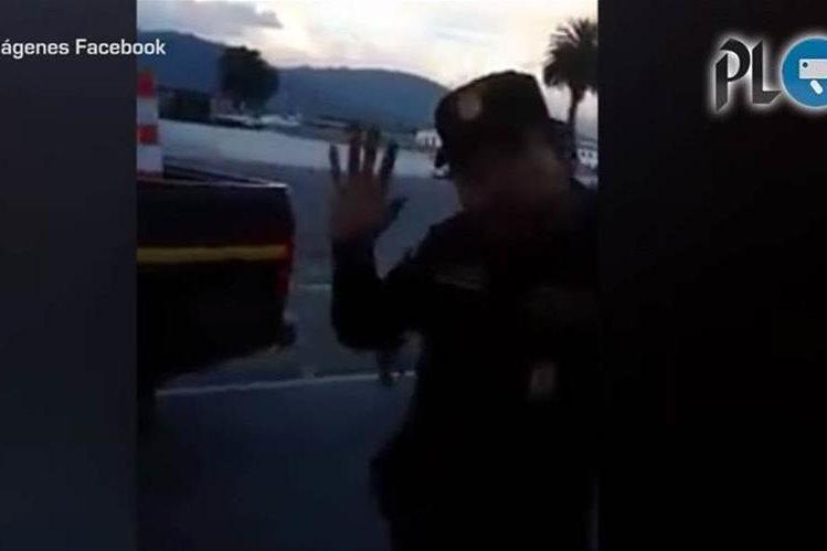 Un agente de la PNC muestra una seña obscena luego de discusión con vecinos de Xela. (Foto Prensa Libre: Facebook)