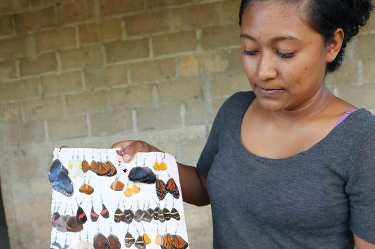 Roxana Guerrero Chacón, experta en cuidar mariposas, muestra que de los insectos fallecidos hacen llaveros y aretes. (Foto Prensa Libre: Rigoberto Escobar).